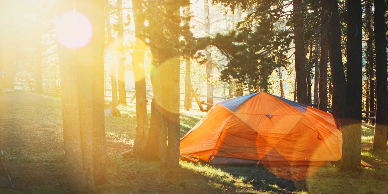 Tent in forrest with sun in background