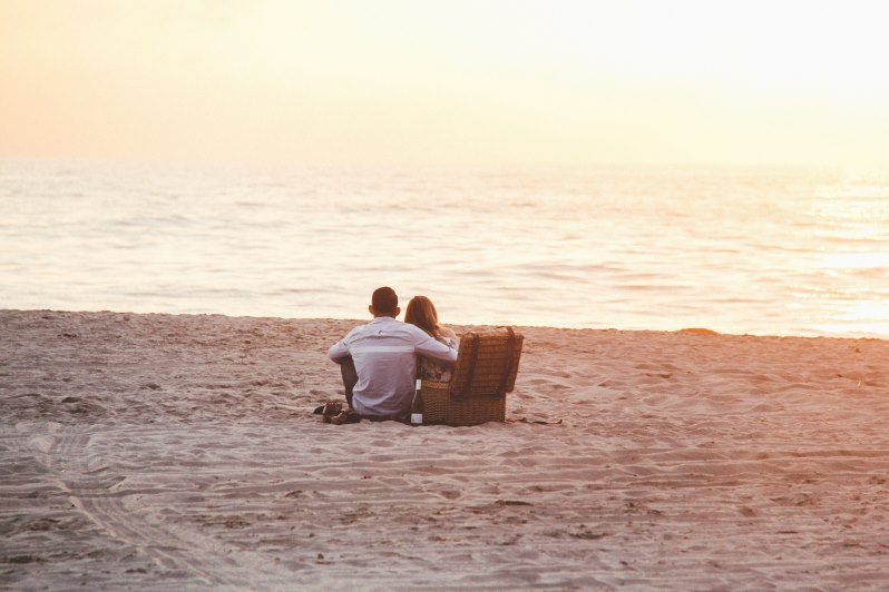 Couple sitting in the sand, having a picnic