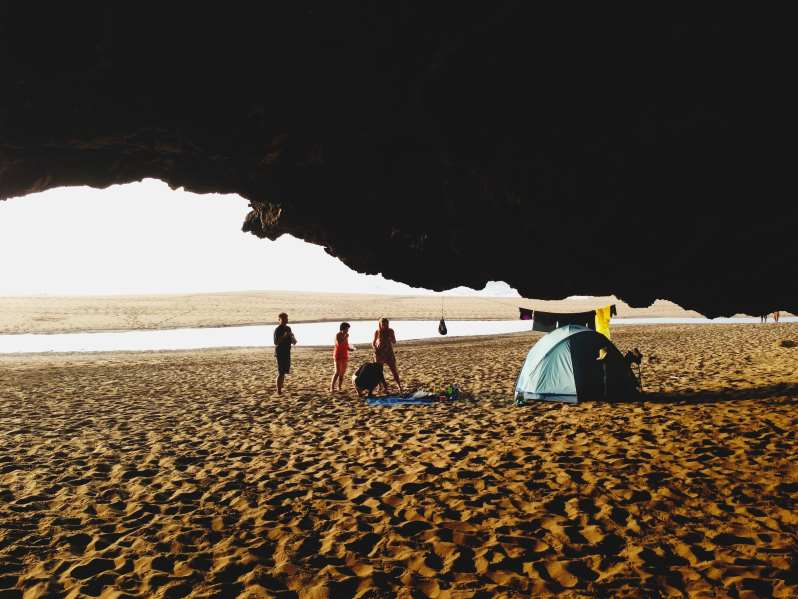 Tent on beach outsive cave