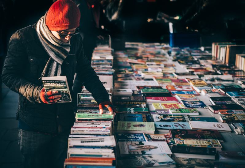 Man looking at books at a yard sale